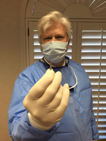 Dr. Kosinski wearing a mask and surgical uniform, holding up an implant with his gloved hand